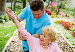 Senior woman with arthritis in her shoulder receives physical therapy in outdoor setting
