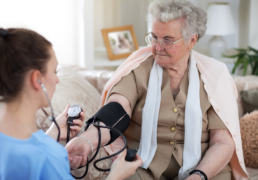Nurse in home visit measuring blood pressure of old woman