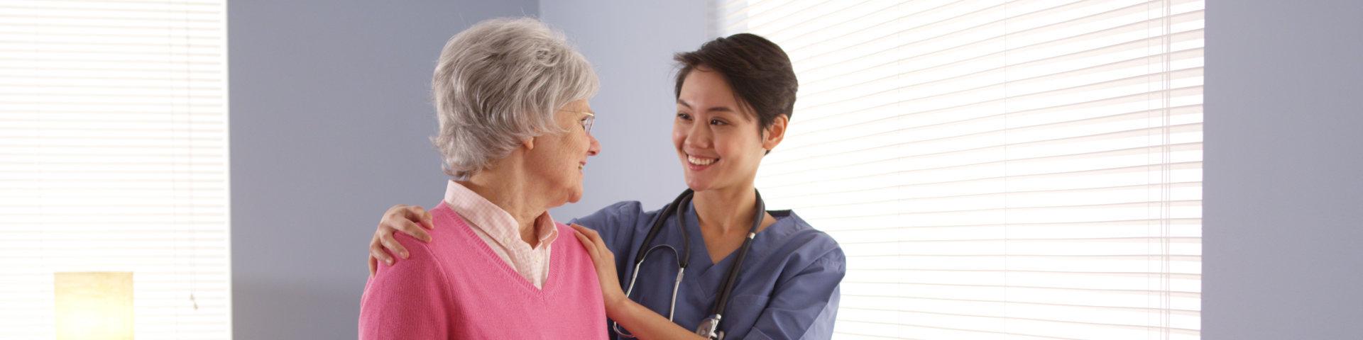 Nurse and elderly patient standing by window