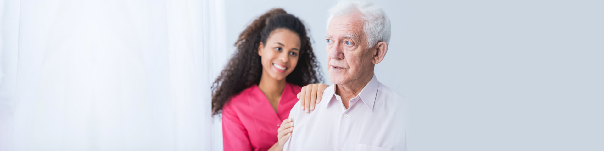 Female carer assisting and supporting senior man