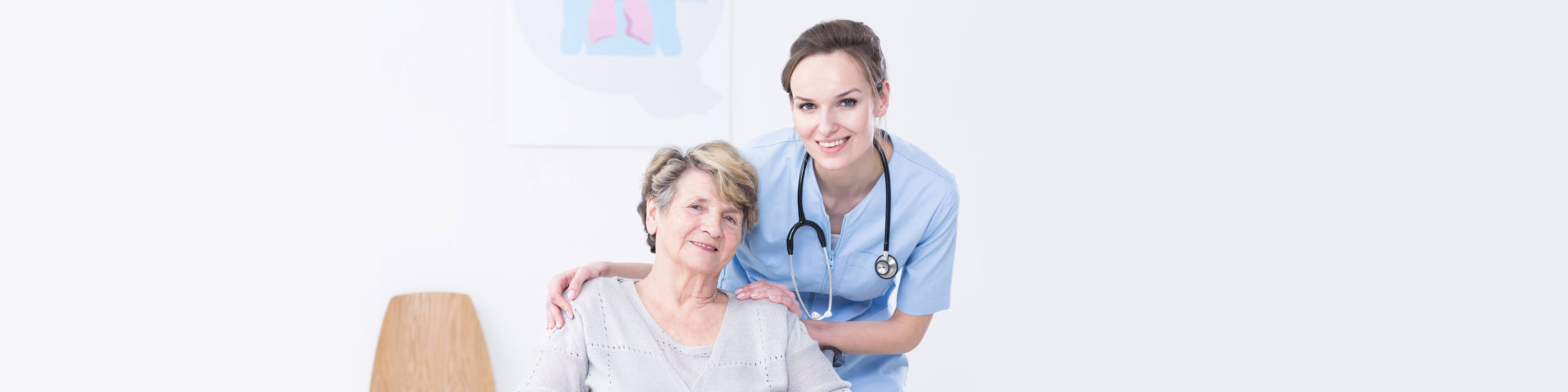 Young, smiled doctor standing behind the elder women with hands on senior's shoulder