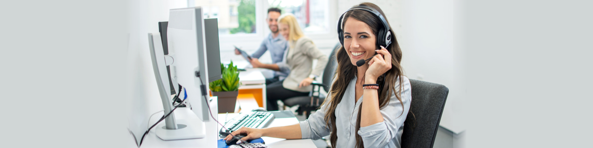 Smiling friendly female call-center agent with headset